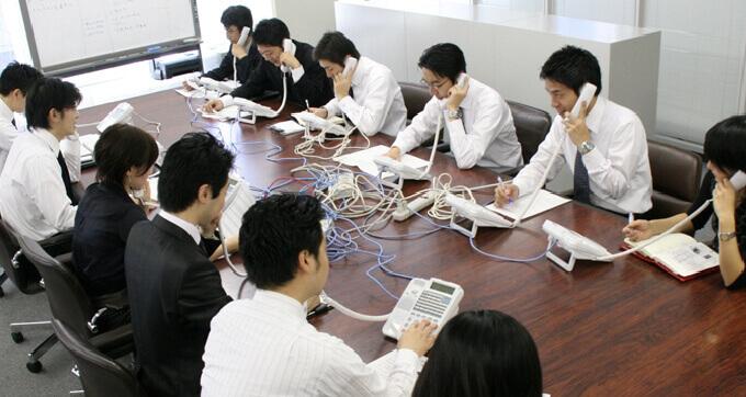 出展予定企業や海外バイヤーに、社員同士励まし合いながら一斉に電話をかける社員たち